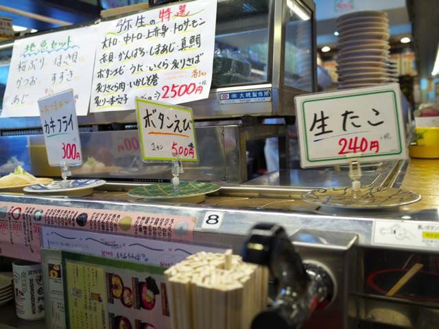 回転寿司レーンを流れるメニューの札