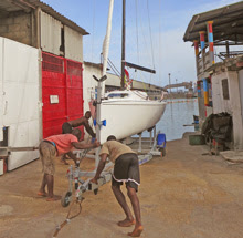 J/70 one-design sailboat- being hand-launched on ramp in Togo