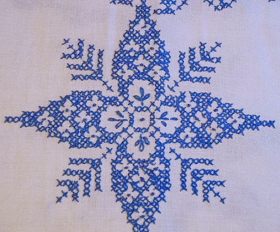 blue snowflake cross-stitched on white linen