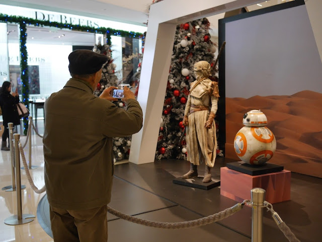 elderly man taking a photo of a Star Wars display at the IAPM shopping center in Shanghai