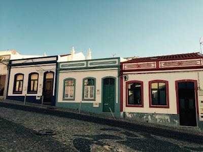 Tre like hus i ulike farger.