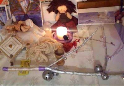 """Altare dedicato a Brigid, di Laura Ghianda. Si vedono immagini di Brigid, della ruota dell'anno, un """"occhio di brigid"""", la cintura di Brigid, la bambolina di Brigid, una candela, e il ramo d'argento con i campanellini"""