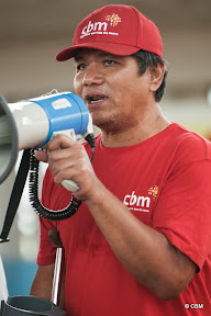 A man speaking into a megaphone (he's wearing a red cap and t-shirt branded 'CBM' and uses a crutch for mobility