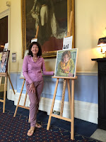 Stella Tooth with her portrait of Geraldine Sharpe Newton at the IoD Portrayed! show