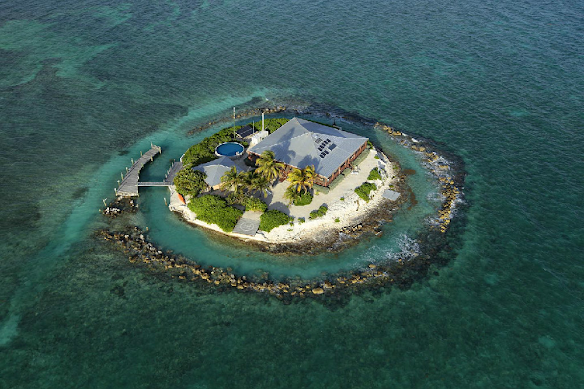 Photo of a single house covering most of the land mass of a small island in the ocean.