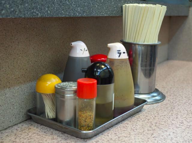 店内のカウンター上。調味料と割り箸が置かれてる。