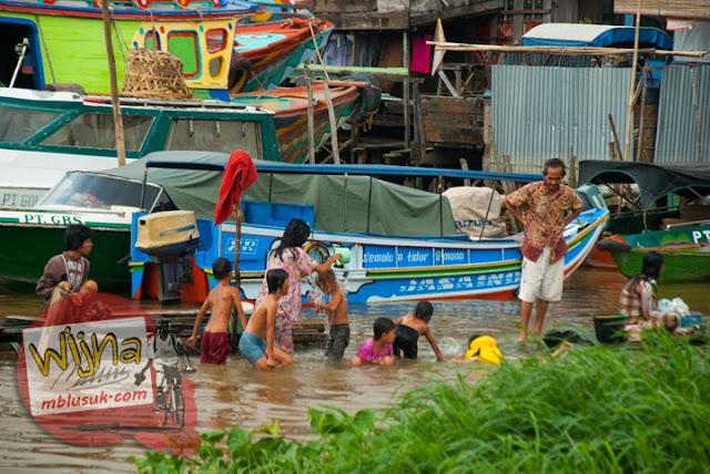 Anak-anak, orang tua, serta gadis muda yang tinggal di pemukiman di Tepi Sungai Musi mandi telanjang di Sungai Musi Palembang Sumatera Selatan