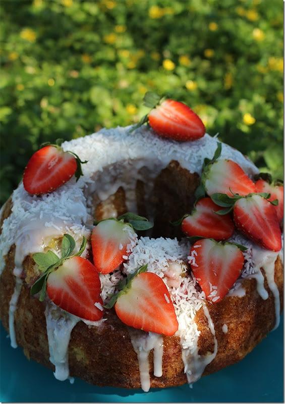 Närbild på kakan täckt av rinnande glasyr, kokosflingor och färska jordgubbar.