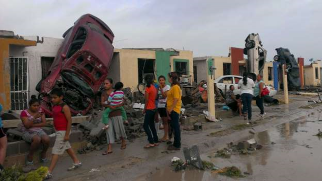 A tornado raged through the U.S.-Mexico border on 25 May 2015, destroying dozens of homes and wrecking cars. According to the BBC, around 13 people were killed by the tornado that hit the northern Mexico border city of Ciudad Acuna. (Pictured) Residents stand outside their homes as damaged cars are seen. Photo: Reuters