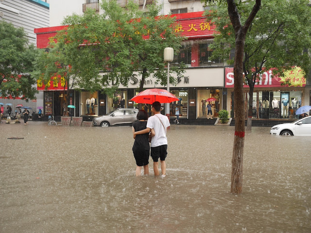 young man and woman with umbrella on a flooded street in Taiyuan, China