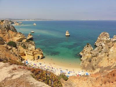 Utsikt ned mot en strand med klipper på sidene og ute i havet.