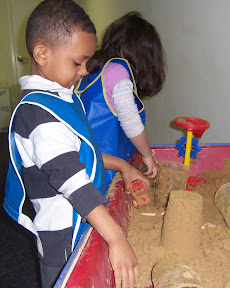 Children build with wet sand at a sensory table.