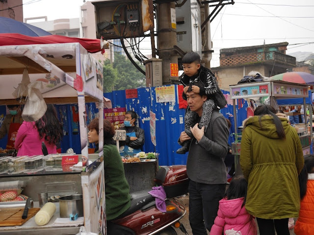 man carrying a little boy on his shoulders past street food vendors in Ningde, China