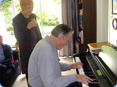 Roy Steen tickling the ivories with Edith Fyfe observing. Photo courtesy of Dennis Lyons.