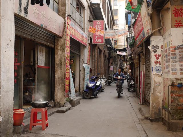 man riding a motorbike on Wuya Lane in Shaoguan, Guangdong