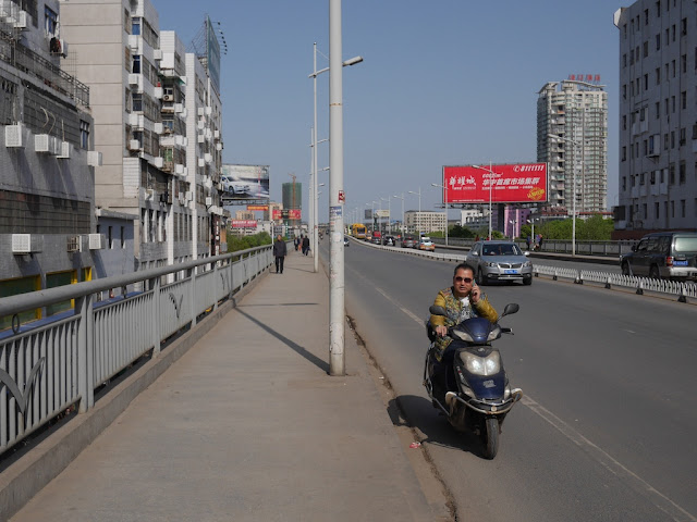 man using a mobile phone while driving a motorbike