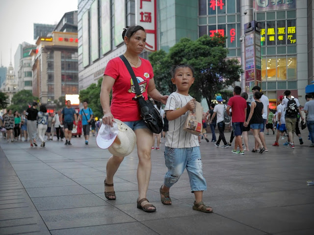 woman walking with boy holding a McDonald's bag