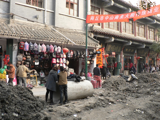 woman holding a child who is standing on a large concrete tube at the Zhongshan Main Street in the Shangqiu Ancient City (商丘古城)