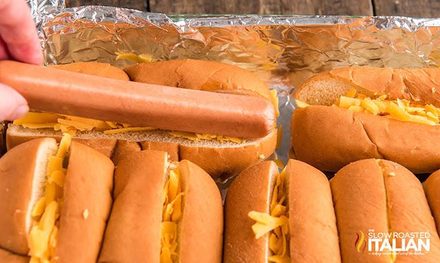 placing a hot dog on a bun