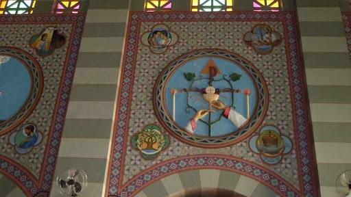 """Na figura: A Cruz monogramática do Cristo Salvador dominando o quadro; encimando o """"P"""", triângulo (Ssma. Trindade), do Altar, onde ardem dois candelabros (Fé no mistério). Duas mãos seguram o Cálice e sobre ele dois cachos de uvas (vinho); no cruzamento das hastes da Cruz a Hóstia branca, com a Cruz que simboliza o Cristo depois da consagração. Na legenda, as palavras da Consagração: """"Accipite et manducate"""" (Tomai e Comei). Mt. 26, 26"""