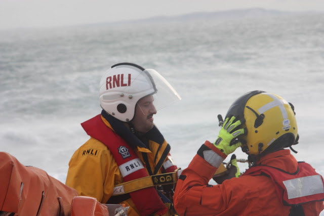 9 October 2011. Crew Member Dave Leabourne prepares to be winched up during a training exercise with Portland helicopter 106. Photo: Poole RNLI/Ade