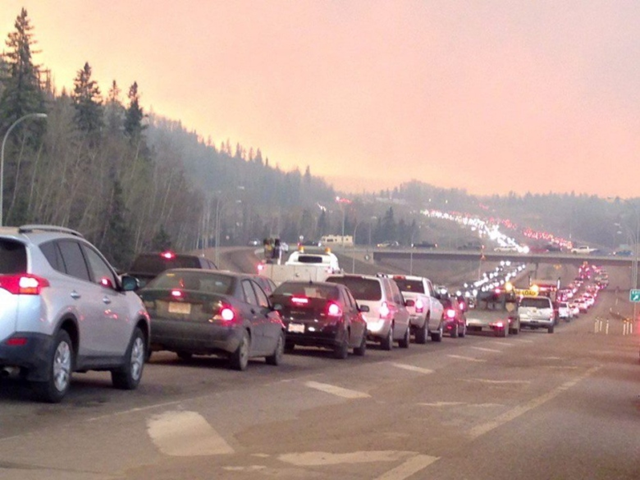 Smoke fills the air as cars line up on Highway 63 out of Fort McMurray on 3 May 2016, where traffic is gridlocked following the mandatory evacuation order. Photo: CAOS91.1 (KAOS) / Canadian Press