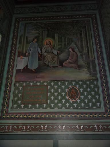 """Parede direita da Capela. Se refere ao texto de Lucas 10, 38-42:""""Estando Jesus em viagem, entrou numa aldeia, onde uma mulher, chamada Marta, o recebeu em sua casa. Tinha ela uma irmã por nome Maria, que se assentou aos pés do Senhor para ouvi-lo falar. Marta, toda preocupada na lida da casa, veio a Jesus e disse: Senhor, não te importas que minha irmã me deixe só a servir? Dize-lhe que me ajude.Respondeu-lhe o Senhor: Marta, Marta, andas muito inquieta e te preocupas com muitas coisas; no entanto, uma só coisa é necessária; Maria escolheu a boa parte, que lhe não será tirada."""" Ao lado do letreiro em latim tem-se o verso da Medalha Milagrosa: O grande """"M"""" tendo sobre si uma cruz é a inicial do nome de Maria. A cruz é a Cruz de Jesus, que morreu por nós. Aos pés da Cruz encontra-se Maria que sofre e nos anima em união completa com Jesus. As doze estrelas representam a coroa da Virgem. As duas pequenas chamas indicam que Jesus e Maria queimam de amor por nós."""