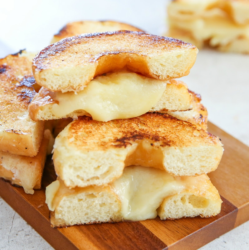 grilled cheese donuts piled on a cutting board