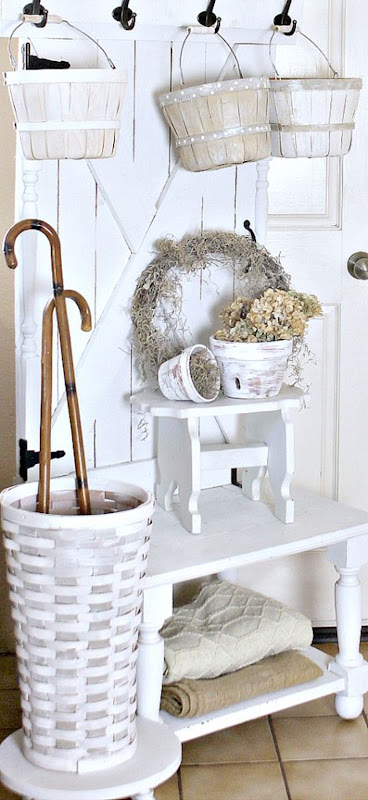 Farmhouse-Hall-Tree-Painted-apple-basketswoven-tall-basket-with-canes-farmhouse-stools-with-aged-pots-and-moss-wreath-blankets