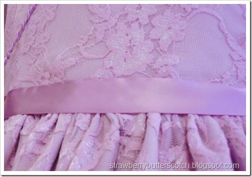 Ribbon at the waist on a pretty pink dress.