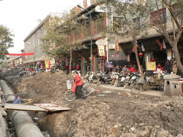 woman pushing her bike towards an informally made bridge over large concrete tubes at a road construction site at the Shangqiu Ancient City (商丘古城)