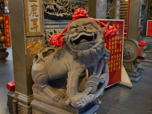 guardian lion with red ribbon bows at the Anping Kaitai Matsu Temple in Tainan, Taiwan