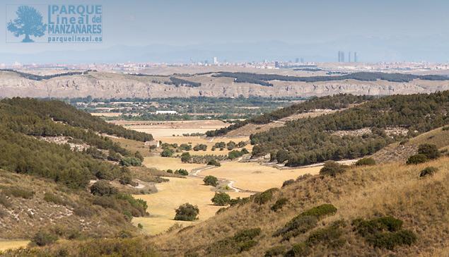 """Magnífica vista desde las cumbres junto al arroyo Torilejos. Se divisa al fondo el valle del Jarama y los cortados  de la Marañosa. Detrás de ellos la ciudad de Madrid con un moderno """"skyline"""" que aún deja ver el edificio de la Telefónica a la izquierda."""