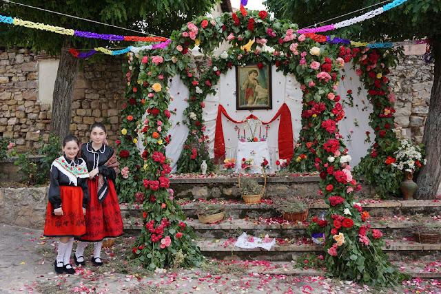 Dos niñas vestidas como seguntinas frente al arco de san juan levantando en la plazuela del mismo nombre