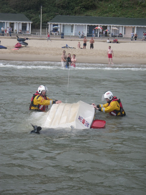 1 September 2012 - the crew members prepare to right the upturned motorboat.  Photo credit: Poole RNLI/Dave Riley