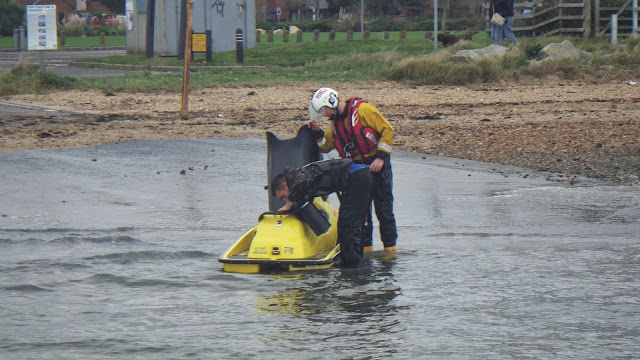 A crew member inspects the broken down jet ski with its owner, after the ILB had towed it to Baiter slipway - 27 October 2014.  Photo credit: RNLI/Poole
