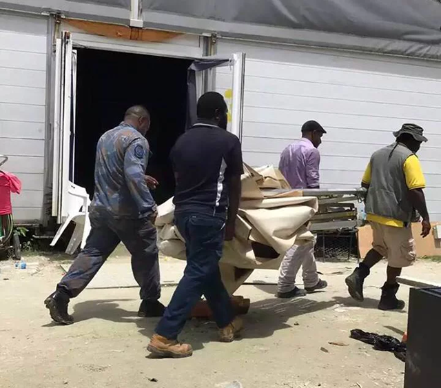 Papua New Guinean officials and police take away makeshift shelters built by refugees and asylum seekers on Manus Island on Friday, 10 November 2017. Photo: The Guardian