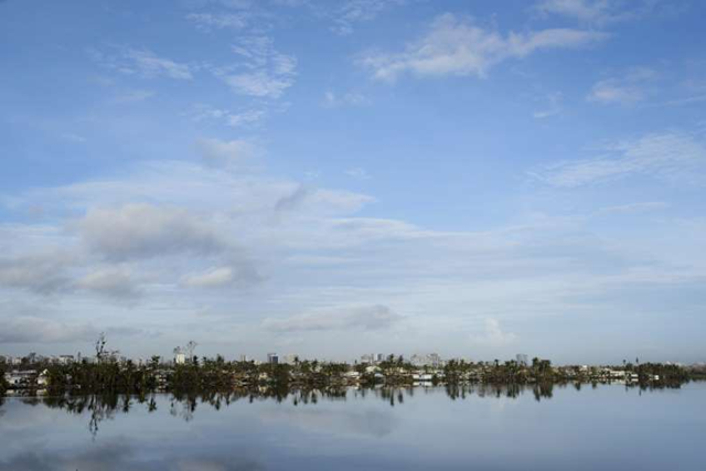 Trees are reflected in the water in the Buena Vista community in the aftermath of Hurricane Maria in San Juan, Puerto Rico on 24 September 2017. Photo: Carlos Giusti / AP Photo
