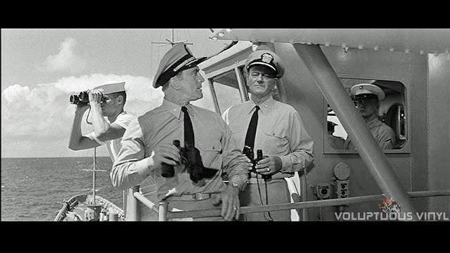 Kirk Douglas and John Wayne on the deck of a war ship.