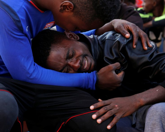 A migrant is comforted by a friend after being rescued, on the Migrant Offshore Aid Station (MOAS) ship Topaz Responder, around 20 nautical miles off the coast of Libya, 23 June 2016. Photo: Darrin Zammit Lupi / REUTERS