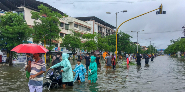 People wade through a flooded street following heavy rains in Vasai Maharashtra on Tuesday 10 July 2018. Photo: PTI