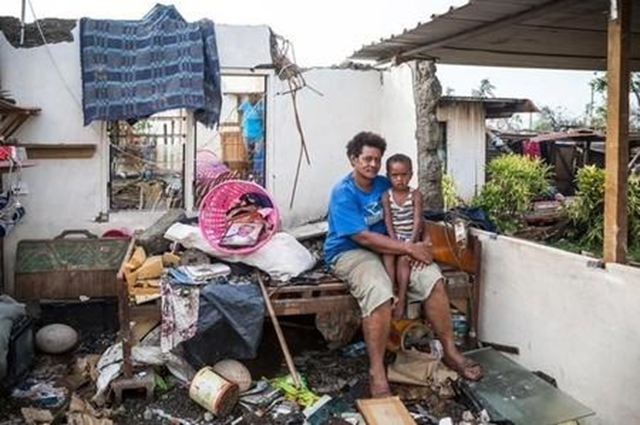 Fijian woman Kalisi holds her son Tuvosa, 3, as she sits on a bed in the remnants of her home damaged by Cyclone Winston in the Rakiraki District of Fiji's Ra province, in this 24 February 2016 handout picture provided by UNICEF. Photo: REUTERS / UNICEF-Sokhin