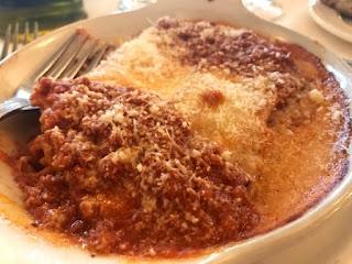 Kjøttsaus under et lag med smeltet ost og med parmesan drysset over.