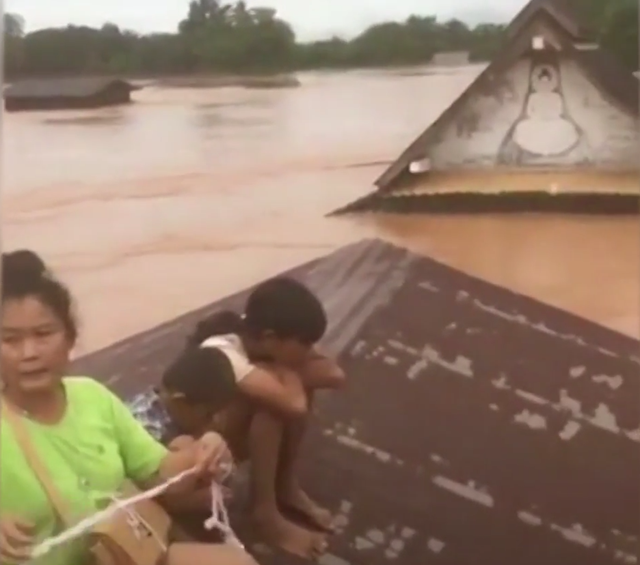 People wait for rescue on a rooftop after a newly built hydroelectric dam broke in southeastern Laos on 23 July 2018, flooding the surrounding countryside and killing at least 24 people. Photo: The New York Times