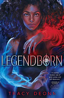A Black girl stares straight forward, one arm sheathed in red flames and the other in blue.