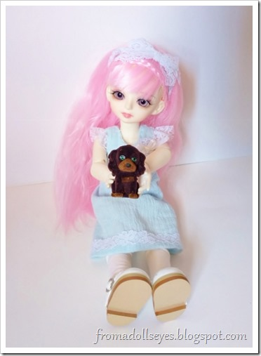 The pink haired bjd (Yuna) holding her new toy puppy.