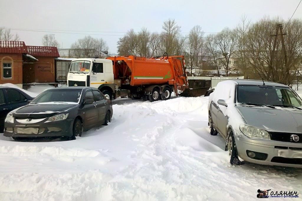 Вывоз мусора из-за сугробов затруднителен, но там, где это уже возможно, мусор вывозится. Тут же видны машины, которые попали в снежную ловушку.