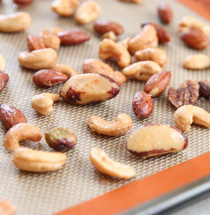 close-up photo of mixed nuts on a sheet pan