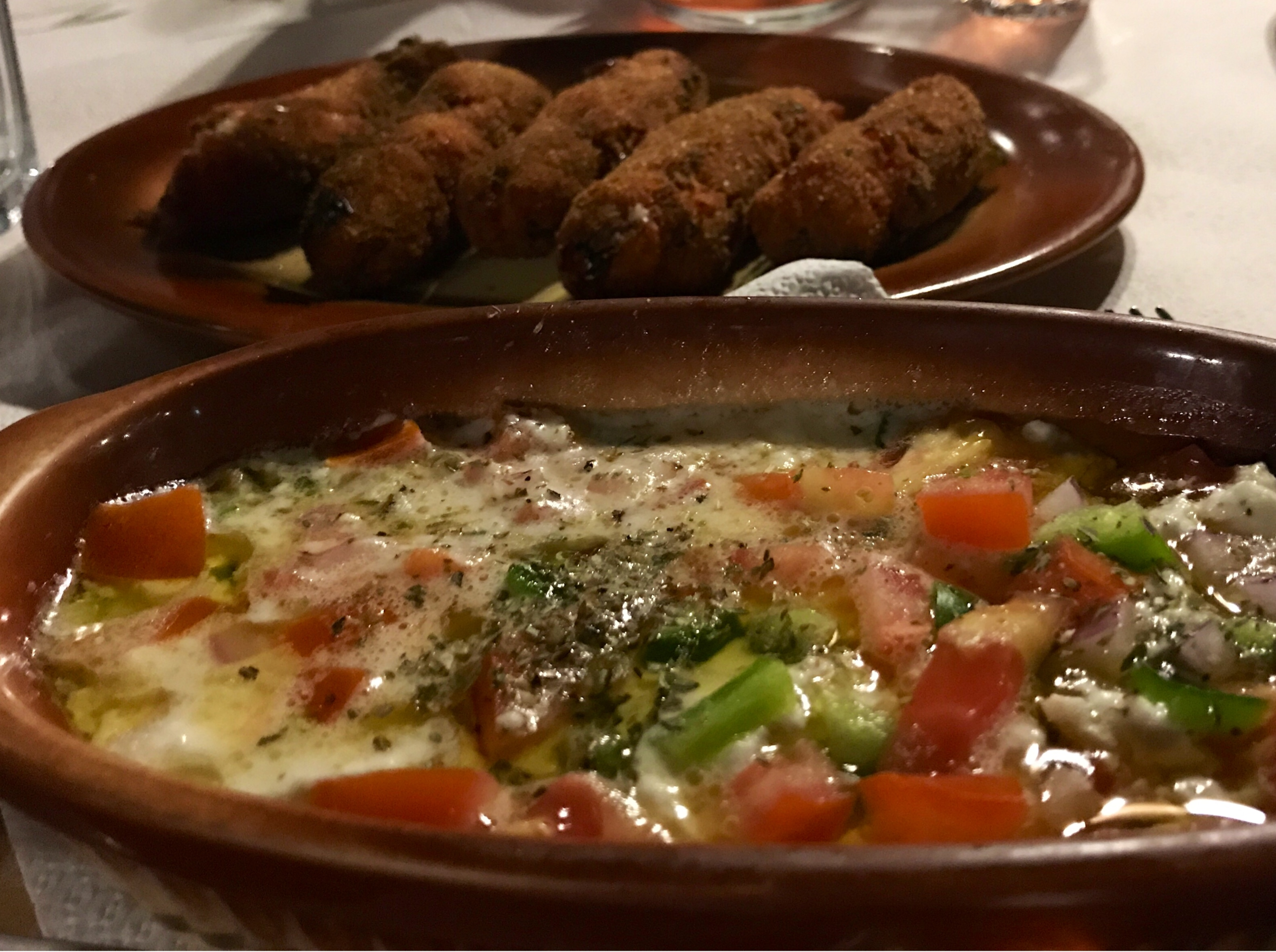 I forgrunnen en keramikkform med smeltet fetaost blandet med grønnsaker. I bakgrunnen noen brune ruller som skal være tomatboller.