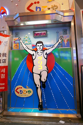 If you're running why a running man is the symbol of a Glico candy company, it's because he is running a 300 meter race, and it so happens that a 300 meter run burns the same amount of calories as eating one piece of Glico caramel.